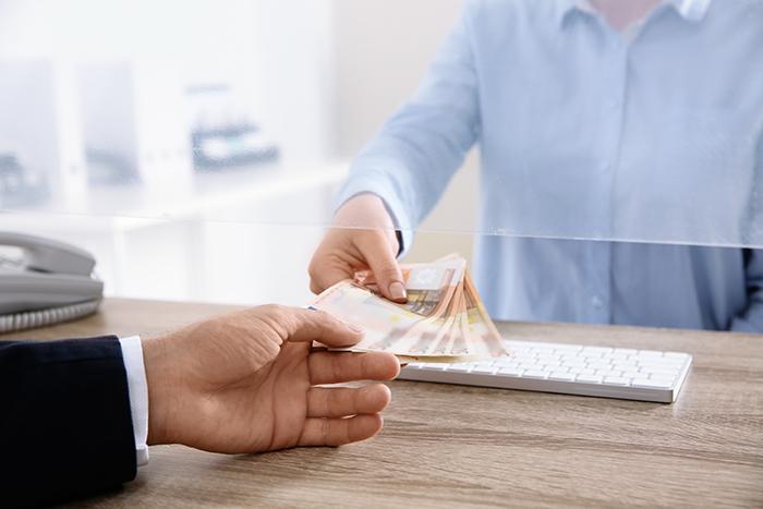 Man receiving money from teller at cash department window, close